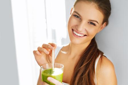 Gezonde Voeding eten. Gelukkig mooie glimlachende vrouw het drinken van groene Detox Plantaardige Smoothie. Dieet. Gezonde levensstijl, Vegetarische Maaltijd. Drinksap. Gezondheidszorg en Beauty Concept. Stockfoto