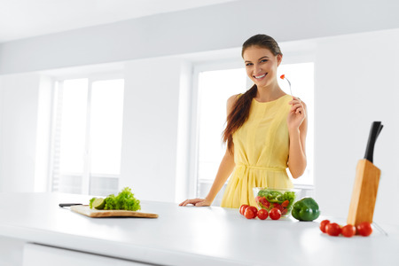 Organic Food. Portrait Of Young Smiling Woman Eating Fresh Healthy Vegetable Salad In Modern Kitchen. Healthy Eating, Meal, Lifestyle Concept. Health, Diet, Fitness. Nutrition. Archivio Fotografico