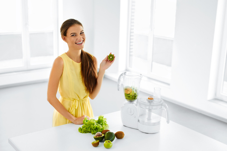 Healthy Nutrition. Closeup Of Smiling Young Woman With Blender Chopping Vegetables For Green Detox Raw Smoothie Juice. Healthy Diet Meal Eating. Vegetarian Food, Dieting.