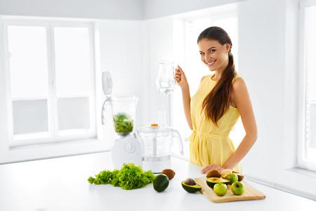 jugo de frutas: Estilo de vida saludable. Feliz sonriente mujer Vegetariana Haciendo Verde Detox Smoothie Blender Vegetal Con el país en cocina. Comida sana, dieta, el concepto de alimentos crudos.