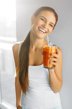 健康的な栄養。幸せな笑顔の菜食主義の女性は新鮮な生のニンジンのデトックス野菜ジュースを飲みます。健康的な食事、食品、ダイエット、ライ
