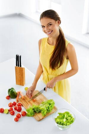 woman diet: Healthy Eating. Close Up Beautiful Smiling Woman Cooking Fresh Organic Food And Making Vegetable Salad In Kitchen. Diet And Lifestyle Concept. Vegetarian Food Preparation. Nutrition.