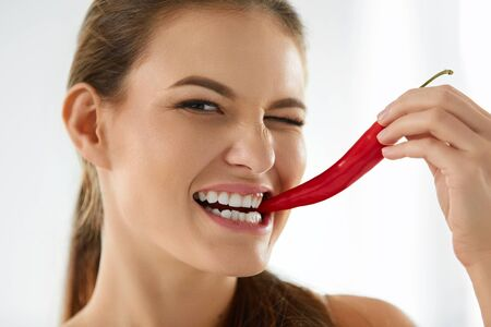 spicy food: Healthy Eating. Close-up Portrait Of Beautiful Young Smiling Woman Biting Spicy Hot Red Chili Pepper. Healthy Lifestyle, Diet And Food Concept. Stock Photo