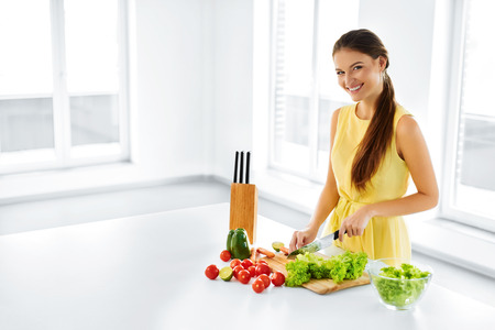 diet dinner: Healthy Food. Happy Smiling Young Woman Preparing Vegetarian Dinner, Cutting Organic Vegetables, Cooking Salad With Knife In Kitchen. Healthy Lifestyle And Eating. Diet, Dieting Concept. Nutrition.