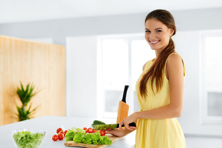 eating salad: Diet. Healthy Eating Woman Cooking Fresh Organic Food And Making Vegetable Salad In Kitchen. Healthy Lifestyle Concept. Food Preparation. Nutrition. Stock Photo