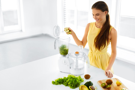blender: Healthy Lifestyle. Happy Smiling Vegetarian Woman Making Green Detox Vegetable Smoothie With Blender Home In Kitchen. Healthy Eating, Diet, Raw Food Concept. Stock Photo