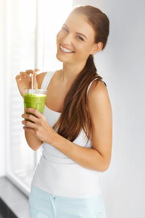 有機食品。新鮮な生緑デトックス野菜ジュースを飲んで健康な食べる女性。健康的なライフ スタイル、菜食主義の食事。スムージーを飲みます。栄