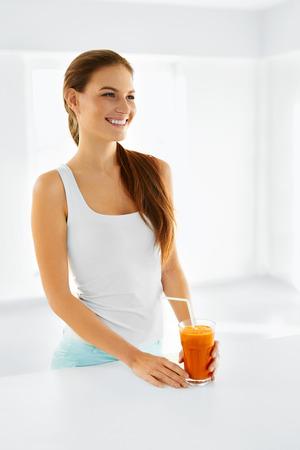 tomando jugo: Nutrición saludable. Feliz Mujer Sonriente Vegetariana Beber cruda fresca Zanahoria Detox vegetal jugo. La alimentación saludable y la Alimentación, la dieta y estilo de vida Concepto. Beba Smoothie. Salud y belleza Concept. Foto de archivo