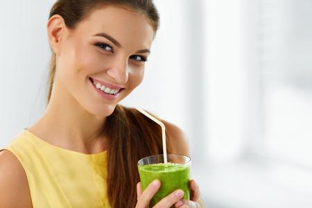 batidos de frutas: Alimentación saludable y comer. Feliz mujer joven que bebe verde Detox vegetal Smoothie. Estilo de vida saludable, dieta vegetariana y comida. Toma jugo. Salud y belleza Concept.