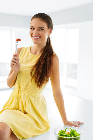 eating salad: Healthy Diet. Beautiful Smiling Woman Eating Fresh Organic Vegetarian Salad In Modern Kitchen. Healthy Eating, Food And Lifestyle Concept. Health, Beauty, Dieting Concept. Nutrition.