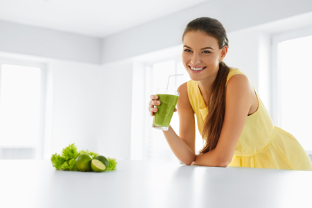 bebidas frias: Comida saludable. Feliz hermosa mujer sonriente que bebe verde Detox Smoothie vegetal. Estilo de vida saludable, la comida y comer. Toma jugo. La dieta, la salud y del de belleza.