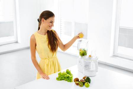 comiendo frutas: Estilo de vida saludable. Feliz sonriente mujer Vegetariana Haciendo Verde Detox Smoothie Blender Vegetal Con el país en cocina. Comida sana, dieta, el concepto de alimentos crudos.