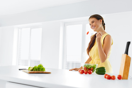 Organic Food. Portrait Of Young Smiling Woman Eating Fresh Healthy Vegetable Salad In Modern Kitchen. Healthy Eating, Meal, Lifestyle Concept. Health, Diet, Fitness. Nutrition. Stock Photo