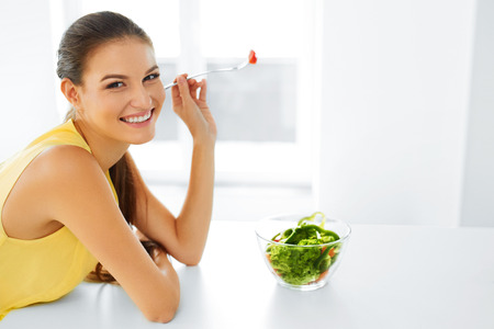 nutrition health: Healthy Eating. Close Up Portrait Of Young Smiling Vegetarian Woman Eating Fresh Healthy Vegetable Salad In Modern Kitchen. Healthy Food, Lifestyle Concept. Health, Dieting, Diet. Nutrition. Stock Photo