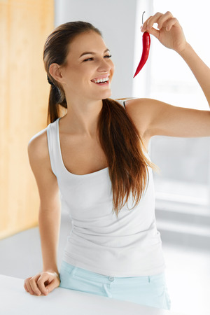 spicy food: Healthy Food. Close-up Of Beautiful Young Smiling Woman Holding Red Hot Chili Pepper. Healthy Lifestyle, Diet And Eating Concept.