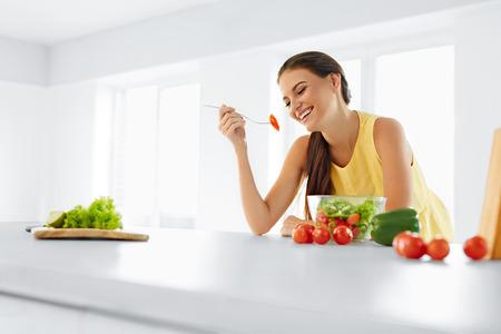 alimentos saludables: Dieta saludable. Hermosa Mujer Sonriente Comer orgánico fresco Ensalada vegetariana en la cocina moderna. Comida sana, Comidas y Lifestyle Concept. Salud, belleza, concepto de dieta.