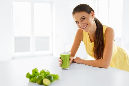 Comida saludable. Feliz hermosa mujer sonriente que bebe verde Detox Smoothie vegetal. Estilo de vida saludable, la comida y comer. Toma jugo. La dieta, la salud y del de belleza. Foto de archivo - 48201505