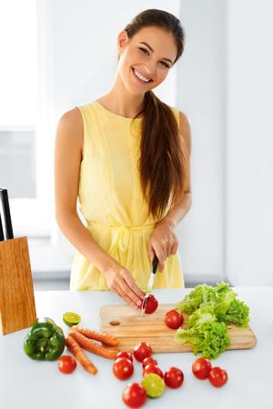 cuchillo de cocina: Comida sana. Feliz sonriente mujer joven que prepara la cena vegetariana, cortar las verduras, ensalada con el cuchillo de cocina en cocina. Estilo de vida saludable y comer. La dieta, el concepto de dieta. Nutrición