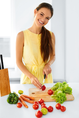 diet dinner: Healthy Food. Happy Smiling Young Woman Preparing Vegetarian Dinner, Cutting Vegetables, Cooking Salad With Knife In Kitchen. Healthy Lifestyle And Eating. Diet, Dieting Concept. Nutrition