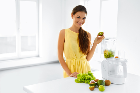 cleanse: Healthy Nutrition. Closeup Of Smiling Young Woman With Blender Chopping Vegetables For Green Detox Raw Smoothie Juice. Healthy Diet Meal Eating. Vegetarian Food, Dieting.