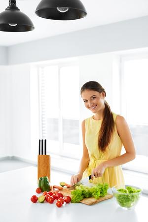cuchillo de cocina: Comida sana. Feliz sonriente mujer joven que prepara la cena vegetariana, de corte Vehículos orgánicos, cocina ensalada con el cuchillo en la cocina. Estilo de vida saludable y comer. La dieta, el concepto de dieta. Nutrición.