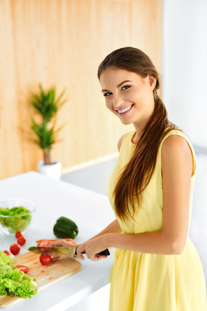 diet dinner: Healthy Woman. Happy Smiling Girl Preparing Vegetarian Dinner, Cutting Vegetables, Cooking Salad With Knife In Kitchen. Healthy Food, Lifestyle And Eating. Diet, Dieting Concept. Nutrition.