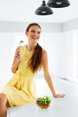 dieta sana: Comida sana. Cierre De sonriente feliz come la ensalada vegetal vegetariana en la cocina moderna. La alimentación saludable y estilo de vida. Salud, belleza, concepto de dieta. Nutrición.