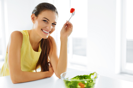 Healthy Eating. Close Up Portrait Of Young Smiling Vegetarian Woman Eating Fresh Healthy Vegetable Salad In Modern Kitchen. Healthy Food, Lifestyle Concept. Health, Dieting, Diet. Nutrition. photo