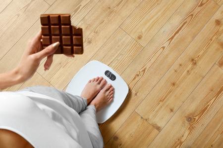 dieta saludable: Dieta. Mujer joven que se coloca en balanza Y Sosteniendo la barra de chocolate. Los dulces son alimentos poco saludables no deseado. El azúcar es malo para la salud. La dieta, la alimentación saludable, estilo de vida. Pérdida de peso. Vista superior