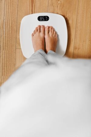 electronic balance: Diet. Top View Of Female Bare Feet Standing On A Scale. Caucasian Young Woman Measuring Body Weight On Weighing Scale At Home. Weight Loss. Dieting; Exercising. Healthy Eating; Lifestyle. Stock Photo