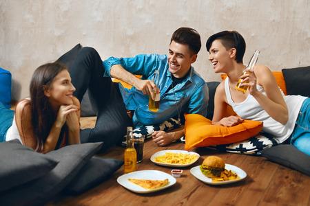mamadera: Comiendo comida. Grupo de j�venes amigos felices de comer comida r�pida papas fritas y refrescos y cerveza fr�a potable mientras est� sentado en el suelo en casa. Celebraci�n, amistad, ocio, el concepto Personas