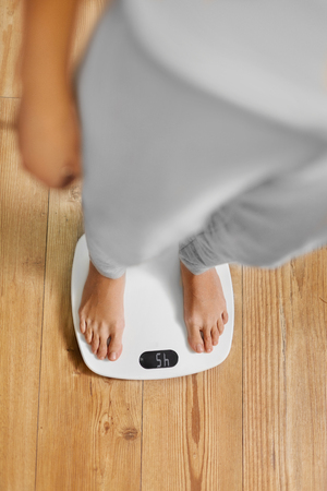 weighing scale: Diet. Top View Of Female Bare Feet Standing On A Scale. Caucasian Young Woman Measuring Body Weight On Weighing Scale At Home. Weight Loss. Dieting; Exercising. Healthy Eating; Lifestyle. Stock Photo