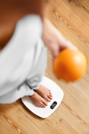 electronic balance: Healthy Food Eating. Female Feet Standing On Scale. Woman Measuring Body Weight On Weighing Scale, Holding Orange In A Hand. Weight Loss. Diet And Dieting, Exercising. Healthy Lifestyle.