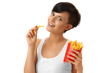 junk: Fast Food. Close-up Of A Smiling Beautiful  Young Girl N Eating Tasty French Fries Chips Against White Background. Unhealthy Junk Food. Lifestyle. Stock Photo