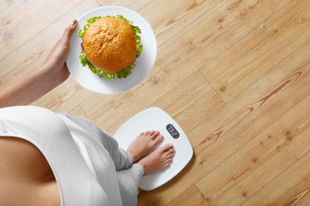 Diet And Fast Food Concept. Overweight Woman Standing On Weighing Scale Holding Burger Hamburger. Unhealthy Junk Food. Dieting, Lifestyle. Weight Loss. Obesity. Top View