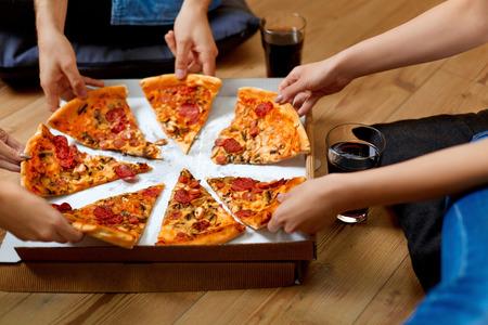 Het eten van pizza. Groep Vrienden Pizza delen samen. Mensen handen nemen van Plakken Van Pepperoni Pizza. Fast Food, Vriendschap, Vrije tijd, Lifestyle. Stockfoto