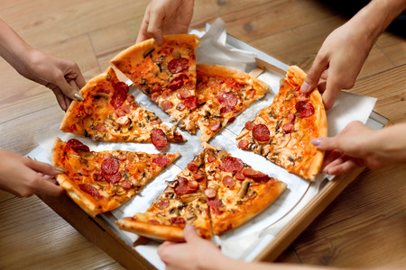 at leisure: Eating Food. Close-up Of People Hands Taking Slices Of Pepperoni Pizza. Group Of Friends Sharing Pizza Together. Fast Food, Friendship, Leisure, Lifestyle.