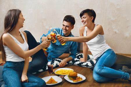 botellas de cerveza: Aclamaciones. Grupo de sonriente feliz Botellas Jóvenes Tostado cerveza y comiendo comida rápida. Amigos De fiesta en casa, sentado en el suelo. Celebración, Amistad, Ocio, Concepto