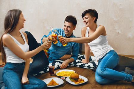 beer drinking: Cheers. Group Of Happy Smiling Young People Toasting Beer Bottles And Eating Fast Food. Friends Partying At Home, Sitting On The Floor. Celebration, Friendship, Leisure, People Concept