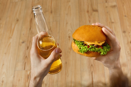 alimentos y bebidas: Eating Fast Food. Closeup Of Mans Hands Holding Classic American Hamburger And Bottle Of Beer. Dinner At Restaurant. Point Of View. Nutrition Foto de archivo