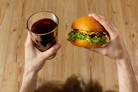 gaseosas: Comer comida rápida. Primer plano de las manos sosteniendo la hamburguesa clásica americana del hombre y vidrio de soda. Cena en el restaurante. Punto de vista. Nutrición Foto de archivo