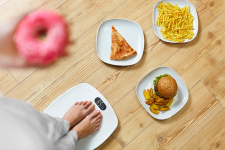 obesity: Diet And Fast Food Concept. Overweight Woman Standing On Weighing Scale Holding Donuts. French Fries, Hamburger And Pizza. Unhealthy Junk Food. Dieting, Lifestyle. Weight Loss. Obesity. Top View