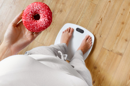 obesity: Diet. Woman Measuring Body Weight On Weighing Scale Holding Donut. Sweets Are Unhealthy Junk Food. Dieting, Healthy Eating, Lifestyle. Weight Loss. Obesity. Top View