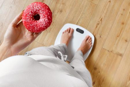 donne obese: Dieta. Donna di misurazione del peso corporeo sulla bilancia della holding della ciambella. I dolci sono malsano cibo spazzatura. Dieta, Alimentazione sana,. Perdita di peso. Obesità. Vista dall'alto