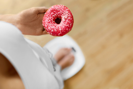 woman on scale: Diet Concept. Young Woman Measuring Body Weight On Weighing Scale While Holding Glazed Donut With Sprinkles. Sweets Are Unhealthy Junk Food. Dieting, Healthy Eating, Lifestyle. Weight Loss. Top View Stock Photo