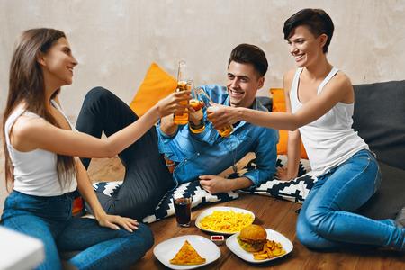 comida rapida: Aclamaciones. Grupo de sonriente feliz Botellas J�venes Tostado cerveza y comiendo comida r�pida. Amigos De fiesta en casa, sentado en el suelo. Celebraci�n, Amistad, Ocio, Concepto