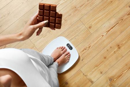 azucar: Dieta. Mujer joven que se coloca en balanza Y Sosteniendo la barra de chocolate. Los dulces son alimentos poco saludables no deseado. El azúcar es malo para la salud. La dieta, la alimentación saludable, estilo de vida. Pérdida de peso. Vista superior