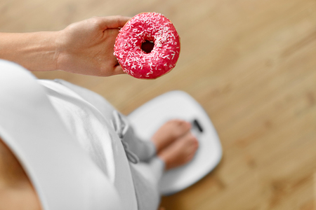 Diet Concept. Young Woman Measuring Body Weight On Weighing Scale While Holding Glazed Donut With Sprinkles. Sweets Are Unhealthy Junk Food. Dieting, Healthy Eating, Lifestyle. Weight Loss. Top View Archivio Fotografico