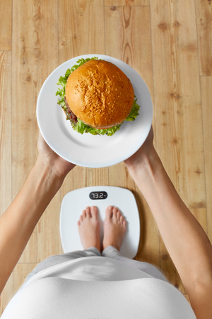 weighing scale: Diet And Fast Food Concept. Overweight Woman Standing On Weighing Scale Holding Burger Hamburger. Unhealthy Junk Food. Dieting, Lifestyle. Weight Loss. Obesity. Top View