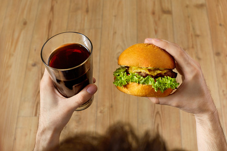 food concept: Eating Fast Food. Closeup Of Mans Hands Holding Classic American Hamburger And Glass Of Soda. Dinner At Restaurant. Point Of View. Nutrition